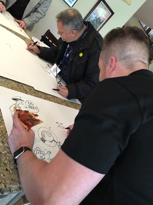Ed Steckley enjoys a pizza while Ray Alma tests how well he can draw without his glasses