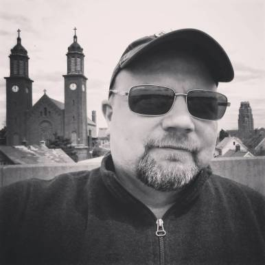 A selfie of me on roof with Corpus Christi Church and Central Terminal in background.