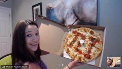 Michelle holding up a TLI pizza