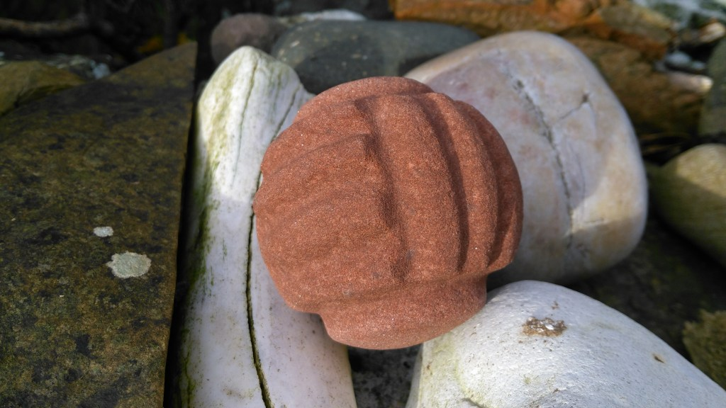 This carved stone ball, in Orkney red sandstone, was made from a drawing by the antiquarian J. W. Cursiter. The original is currently missing.