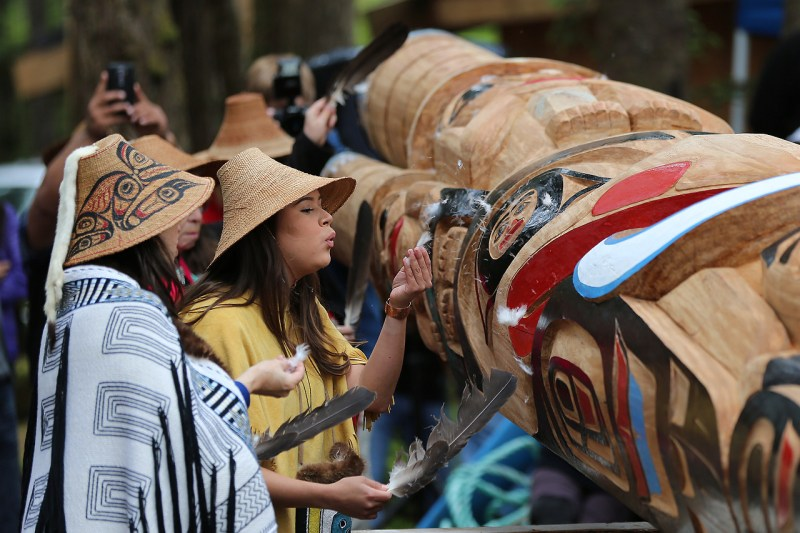 Haida women support their relatives in raising a carved monumental column by master carver Kilthguulans Christian White at Hl'yaalan 'Lngee. The pole was raised in 2017 at Hiellen Longhouse Village, a promising venture in cultural revitalization and economic development. Photograph by Brodie Guy.