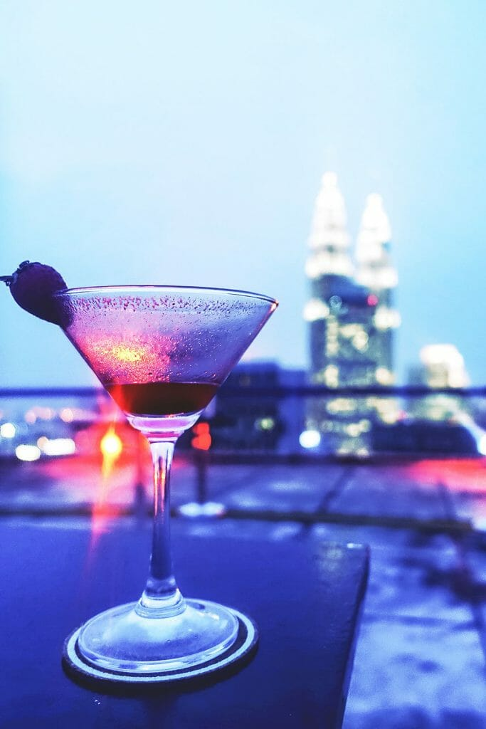 Cocktail glass with strawberry with Petronas Towers in the background