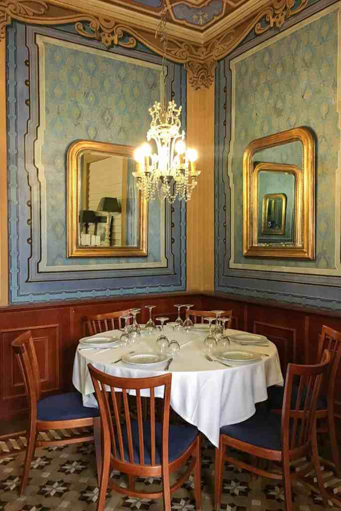 Round table and chairs in an opulent restaurant with chandelier