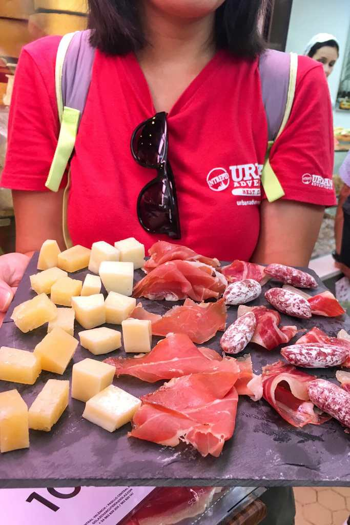 Woman wearing a red t-shirt and holding platter cheese, ham and cured sausage