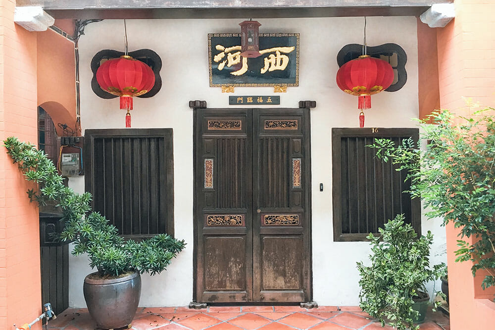 Chinese shophouse with wooden door and two wooden windows and two red lanterns