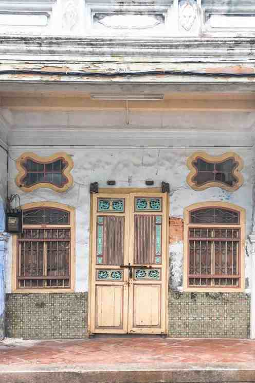 Chinese shophouse with yellow door and two yellow windows