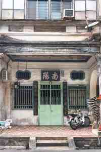 Chinese shophouse with green door and two green windows with scooter parked outside