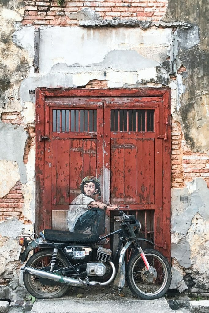 Boy on a motorbike painted on an old door