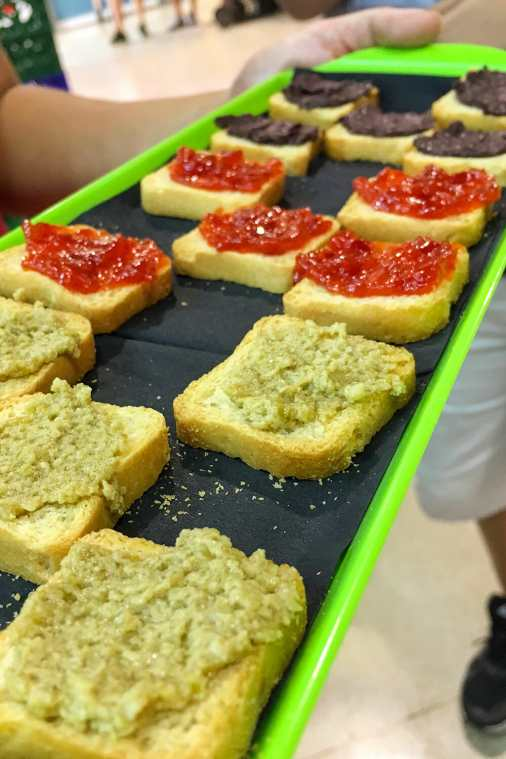 Green tray with melba toast with tapenade and pepper jam on top
