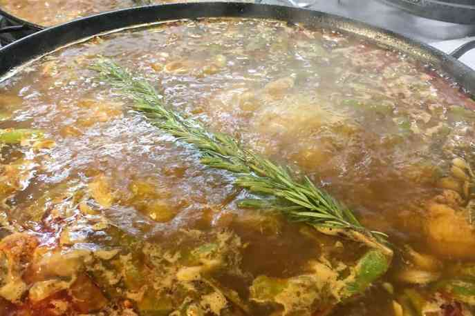 Paella cooking with rosemary sprig infusing in water