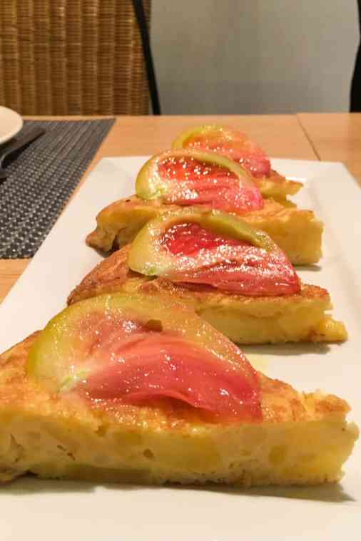 Plate of tortilla slices with tomato on top