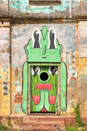Street art piece around a door in an abandoned building in Kochi