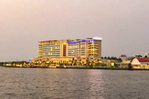 The Grand Hyatt Kochi Bolgatty Hotel at dusk seen from a boat
