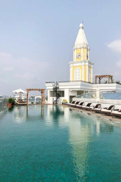 Swimming pool and clock tower on the rooftop terrace of the Fragrant Nature Kochi Hotel