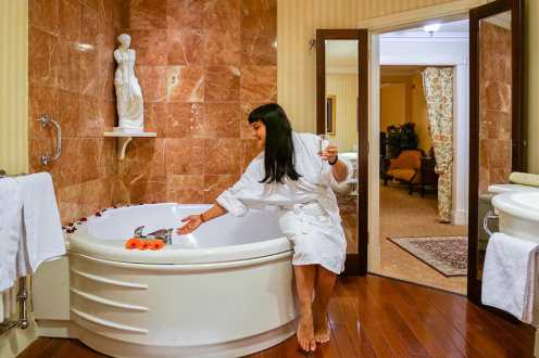 Sitting on the edge of the bathtub while preparing a bath at Harvey's Point Hotel