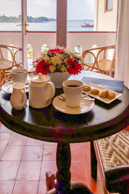 Tea, biscuits and flowers laid out on a small table by a balcony with sea views