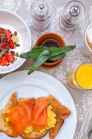 Table with breakfast smoked salmon with scrambled eggs on toast, strawberries, seeds in yogurt and orange juice