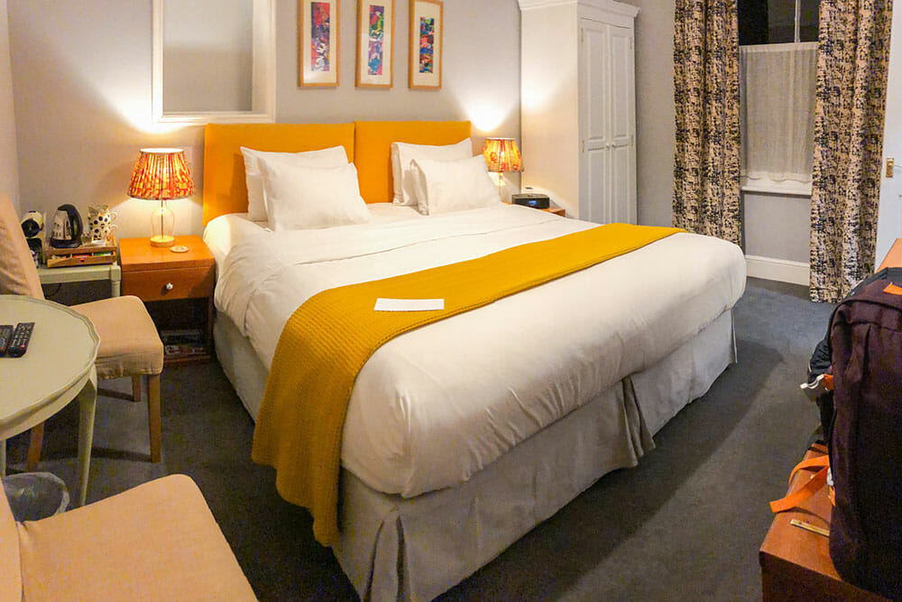 Room at the Parisi Hotel with double bed with yellow headboard and blanket