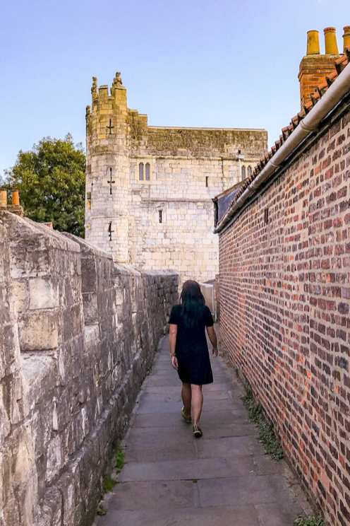 Walking on York City Walls towards Bootham Bar fortified gateway