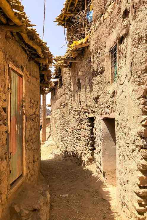Narrow street in a Berber village with houses made of stone and mud
