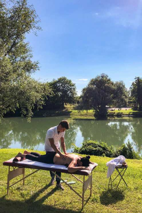 Having a back massage on a table by the river