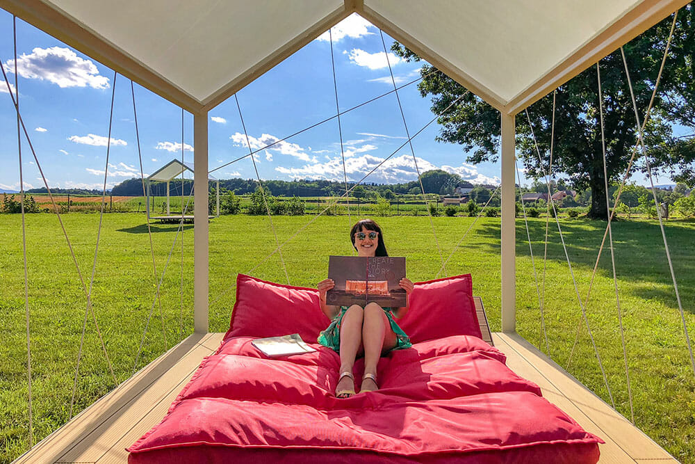 Sitting on the day bed enjoying a magazine with green fields in the back