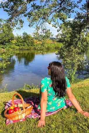 Sitting with a picnic basket on the bank of the river