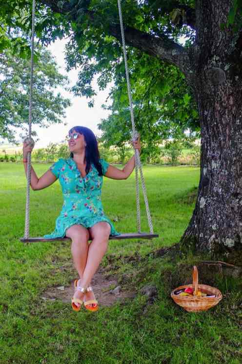 Sitting on a swing that hangs from a tree