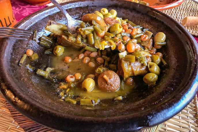 A clay plate with a stew-like meal of lamb, figs, raisins and vegetables