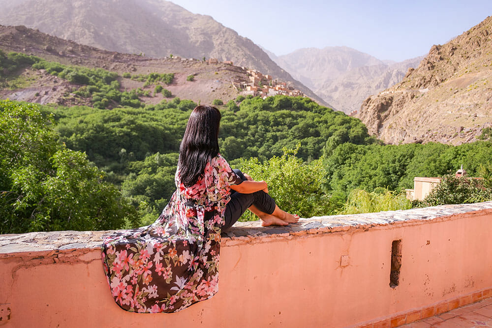 Sitting on a wall looking out to the green valley ahead and Mount Toubkal in the background