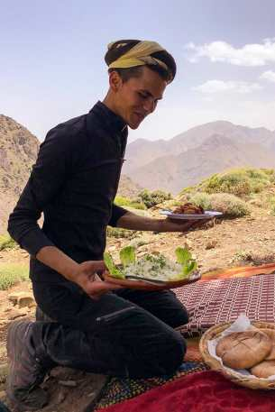 Berber man on his knees on a carpet with two plates of food in his hands ready to serve them