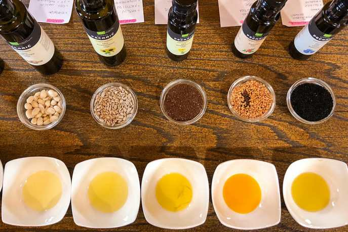 Bottles of oils and bowls of nuts, seeds and oils lined up on a table