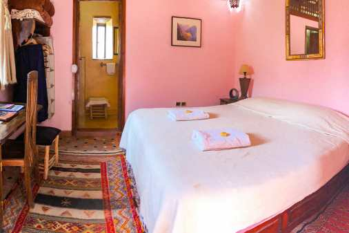 Double bed in a pink room with a traditional Berber carpet
