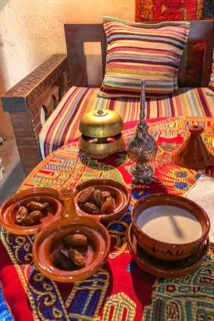 A table with a hotel-style bell, a plate of dates and a bowl of milk