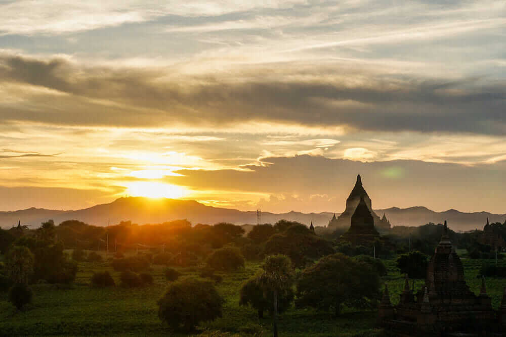 Sunset with silhouettes of stupas on the horizon