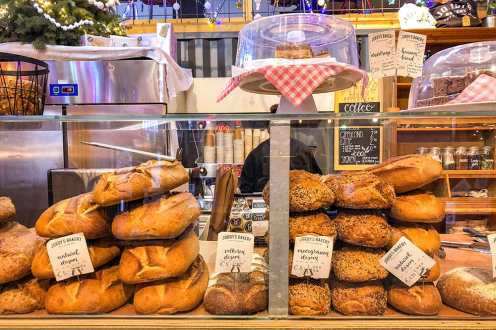 Bread on display inside glass counter in bakery