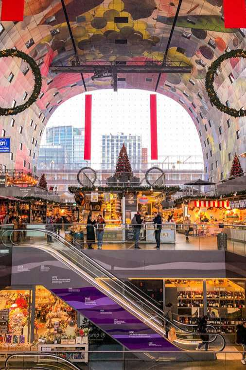 Inside a horseshoe shape building with a painted ceiling with fruit and vegetables and an escalator going down