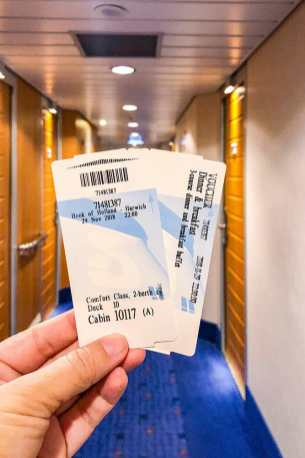 Hand holding two tickets with corridor in the background
