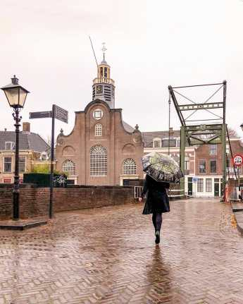 Crossing the bridge towards church with umbrella on a rainy day