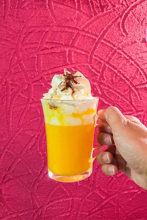 Hand holding a glass with a yellow drink with cream on top against a pink wall