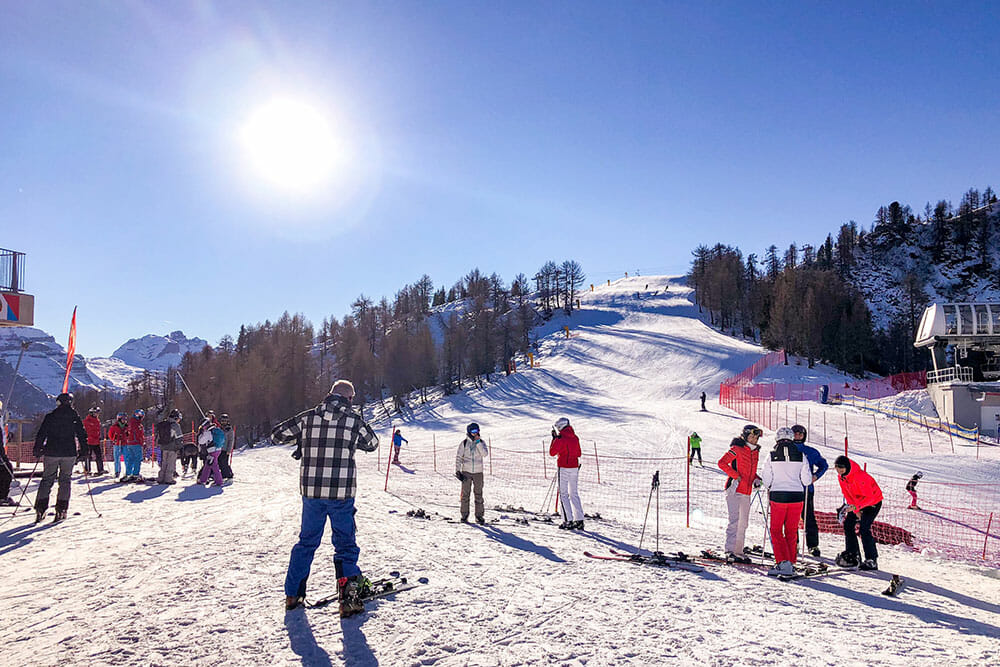 People dressed with skiing gear standing in the snow preparing for skiing, one of the things to do in Trentino in winter