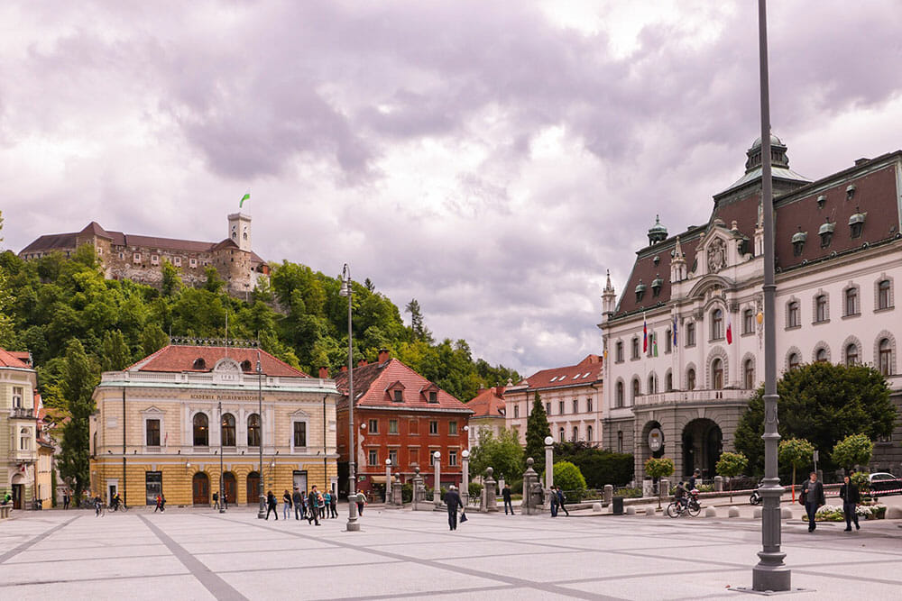 Big square with grand buildings around and castle on top of the hill in the background