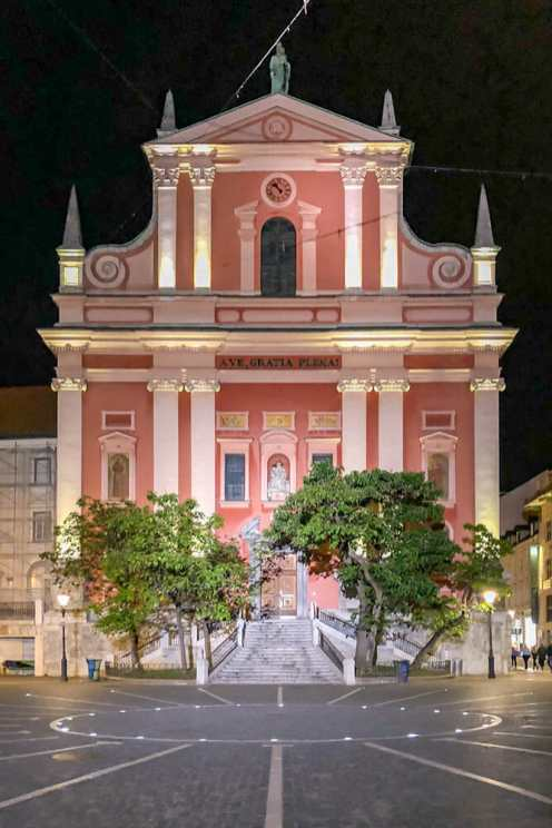 Facade of a pink church lit up at night