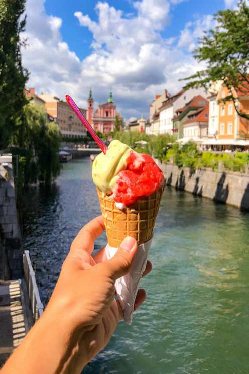 Hand holding a green and red ice cream cone with the river in the background