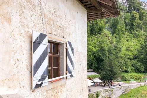 Castle window with striped wooden shutters