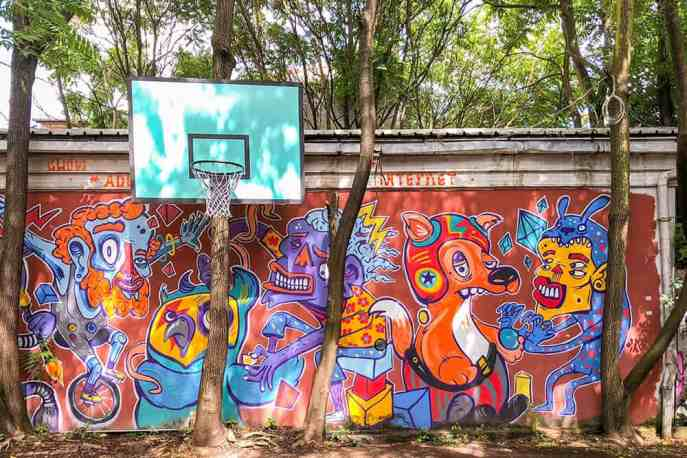 Wall painted with a colourful mural with a basketball ring hanging off a tree