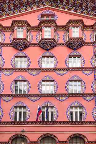 Bright pink facade with highly decorated windows in blue and yellow
