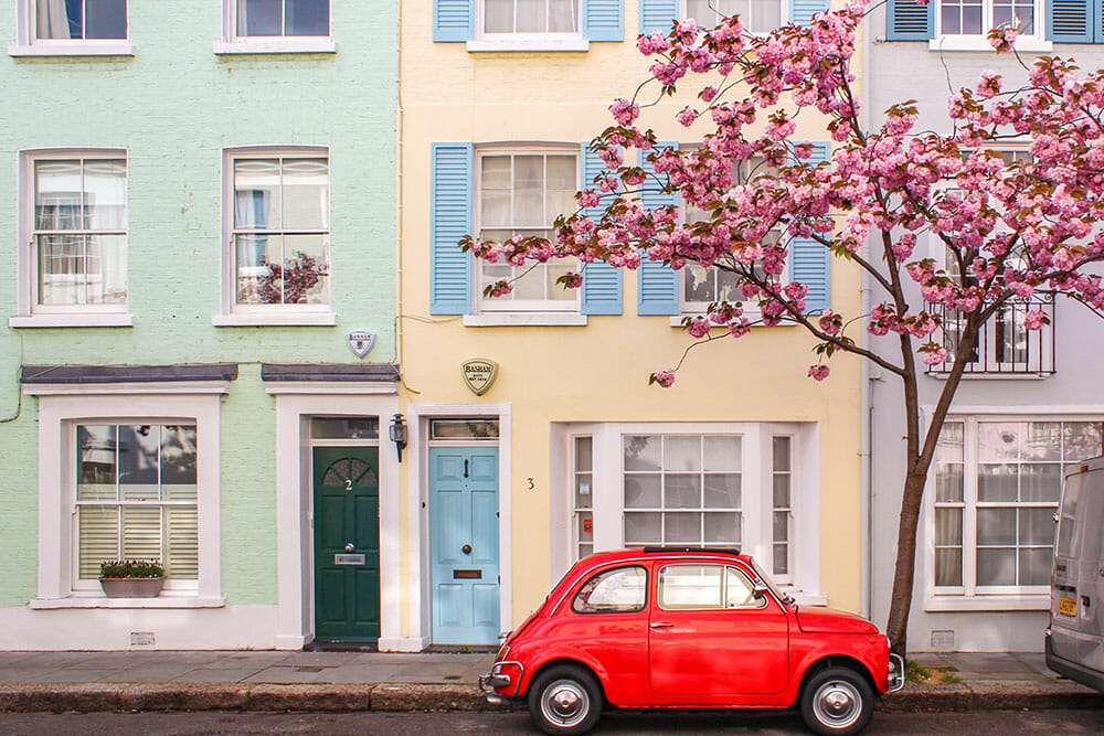 Small red vintage car parked next to a pink cherry blossom tree outside two terraced houses, one mint green and the other light yellow with a blue door and blue window shutters