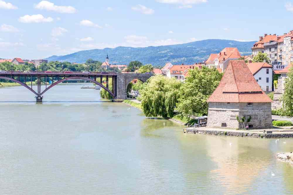 Historical buildings by the river with an iron bridge crossing the river