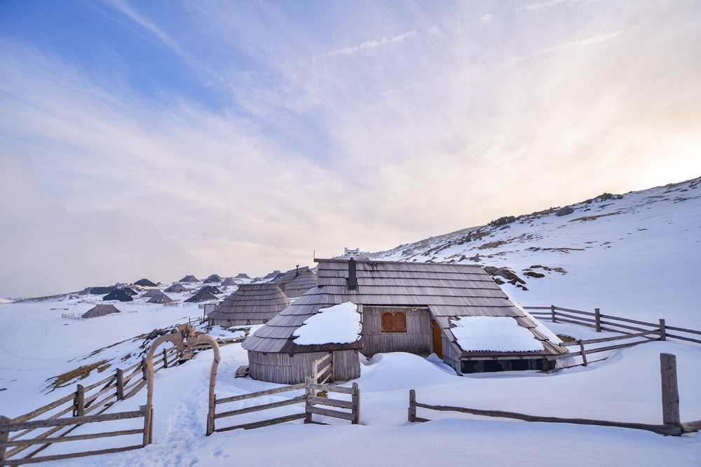 Photo of a wooden hut on a snowy hill with wooden rooftops in the distance